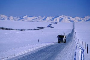 Alaska. Dalton Highway.  Arctic winter. Trans Alaska Pipeline snakes across the tundra next to a truck driving on the highway hauling freight.